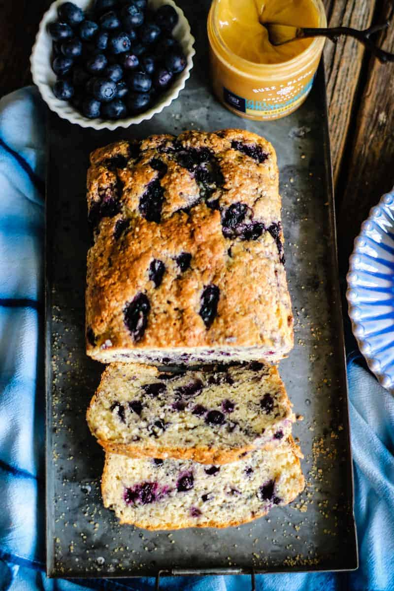 loaf of gluten free blueberry quick bread, sliced with fresh berries and spreadable honey