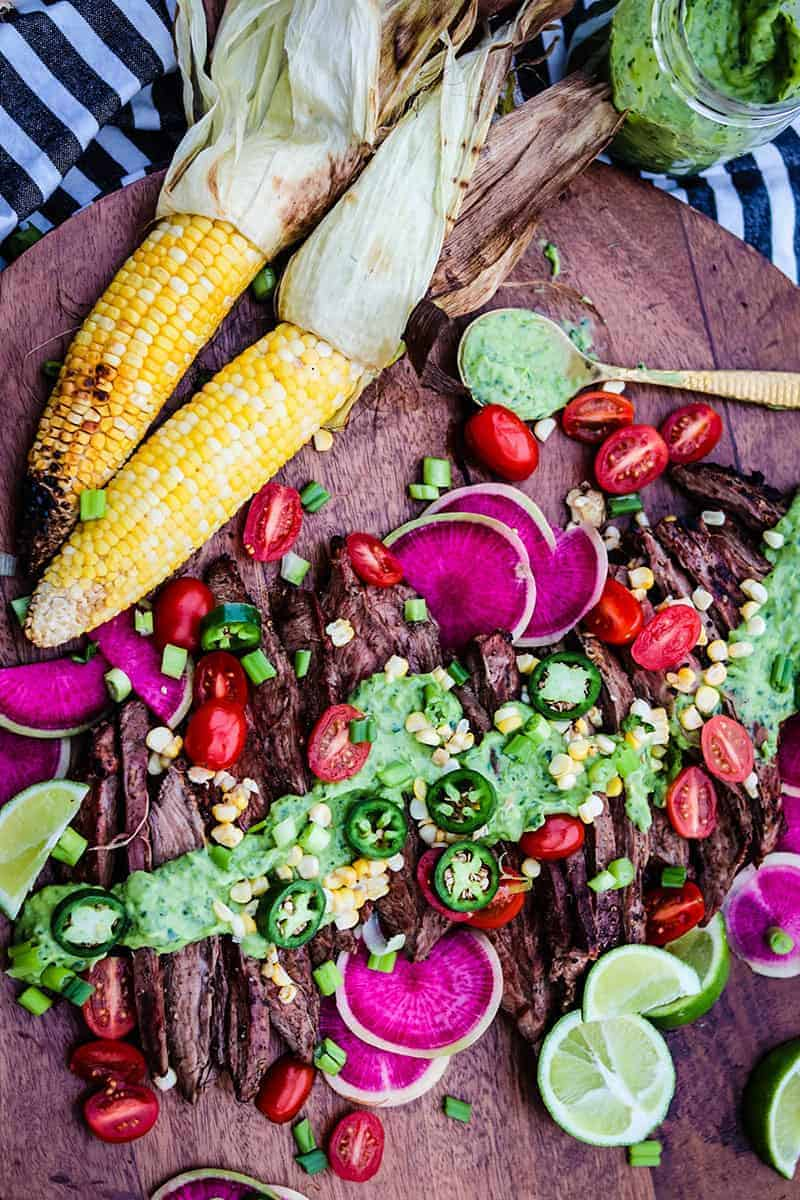 sliced grilled flank steak topped with green goddess sauce and fresh veggies