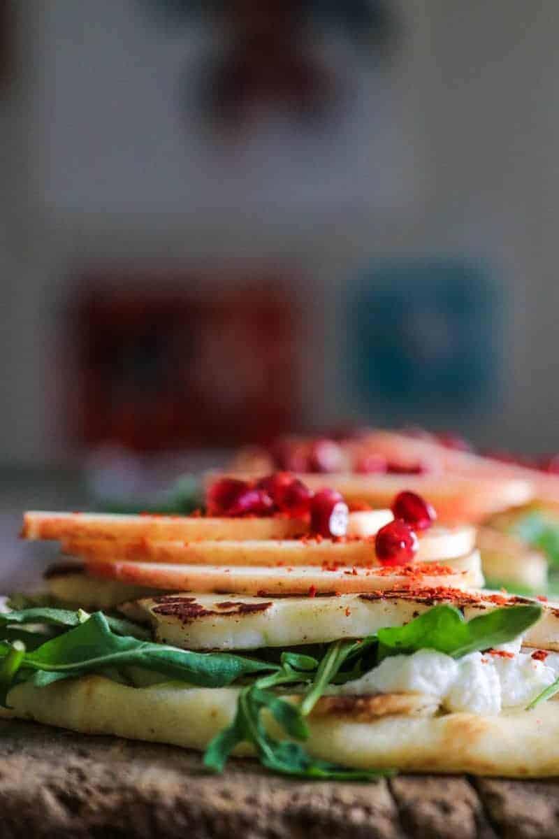Flatbread layered with labneh, arugula, pan seared halloumi cheese, apple slices, aleppo pepper, and pomegranate