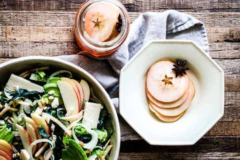 salad with pickled apples and slices of pickled apples in bowl and in jar