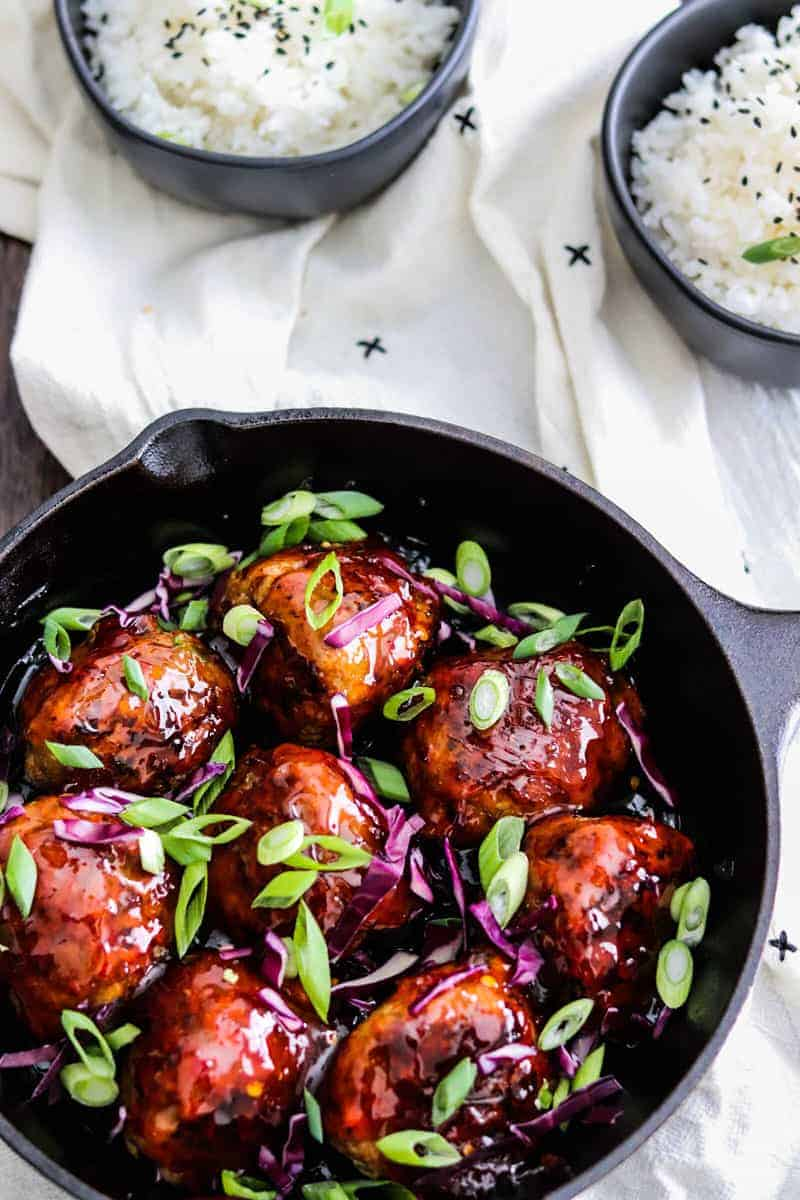 Korean BBQ Meatballs in a skillet with green onions and red cabbage. @ bowls of rice on the side with black sesame seeds.