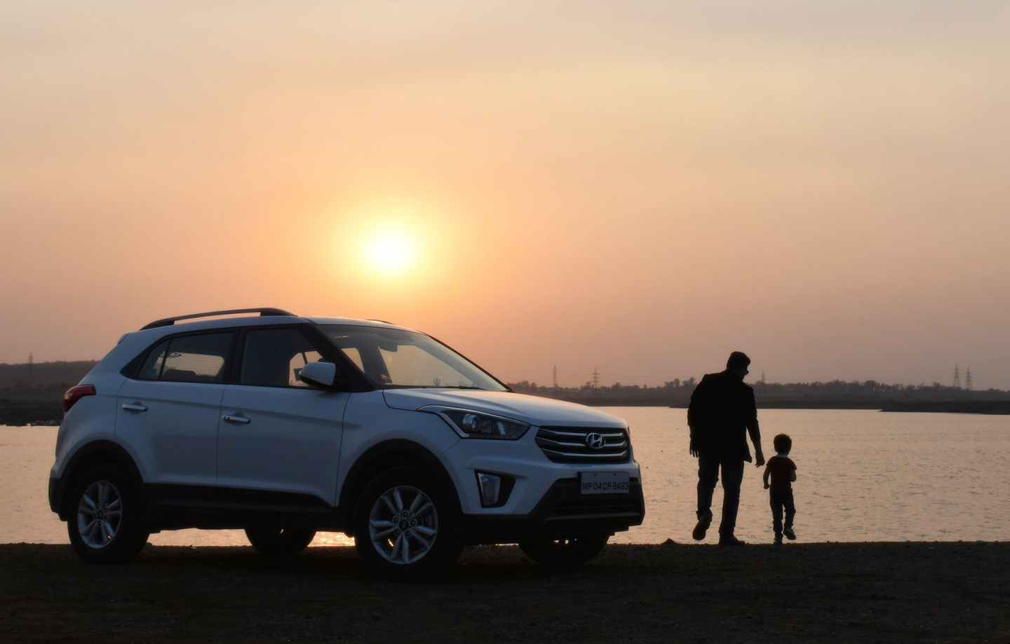 silhouette of man and child near white hyundai tucson suv during golden hour