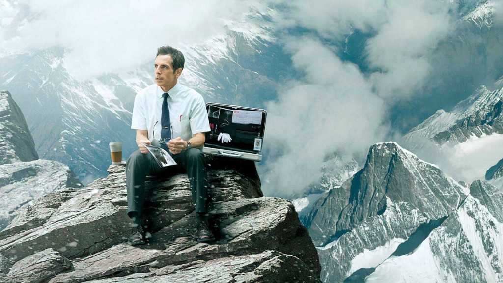 office worker in the snow covered mountain peaks with briefcase