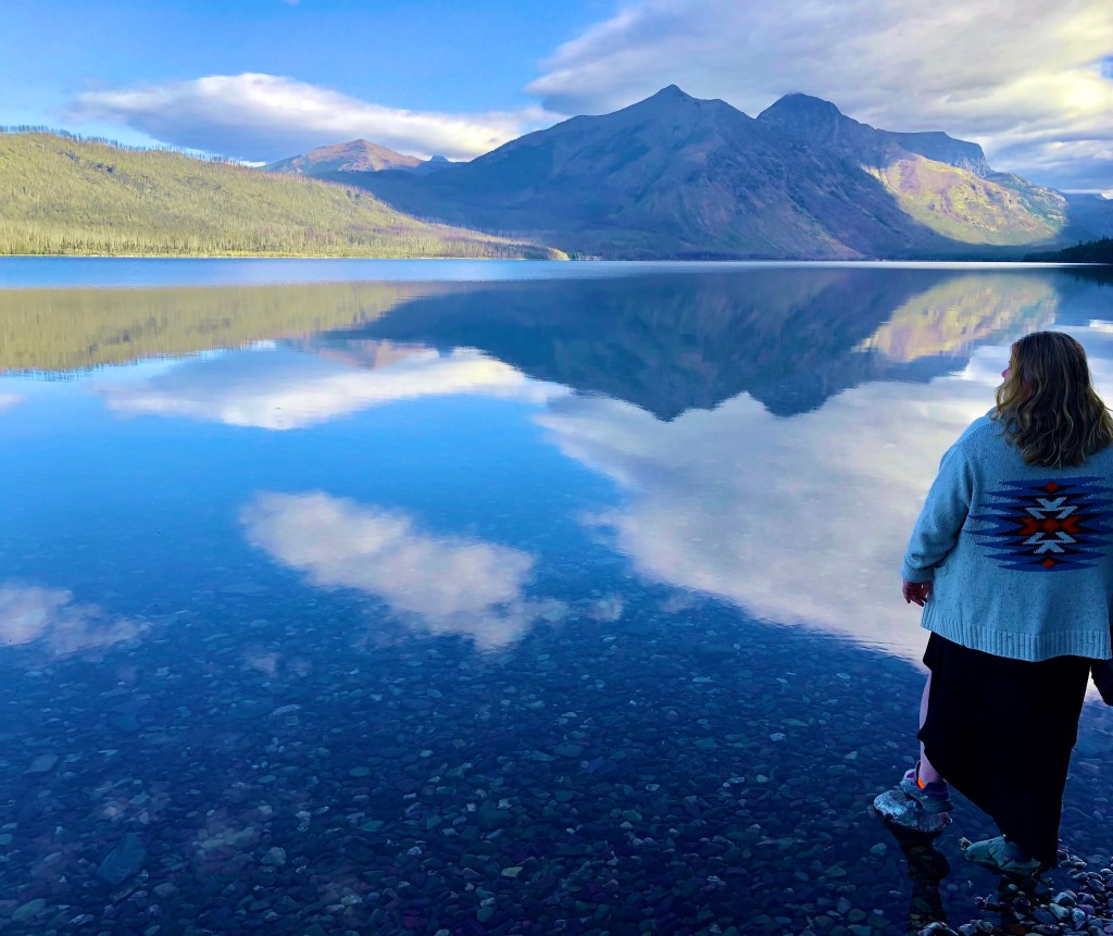 Mountains reflected in the placid lake. Girl walks on water.