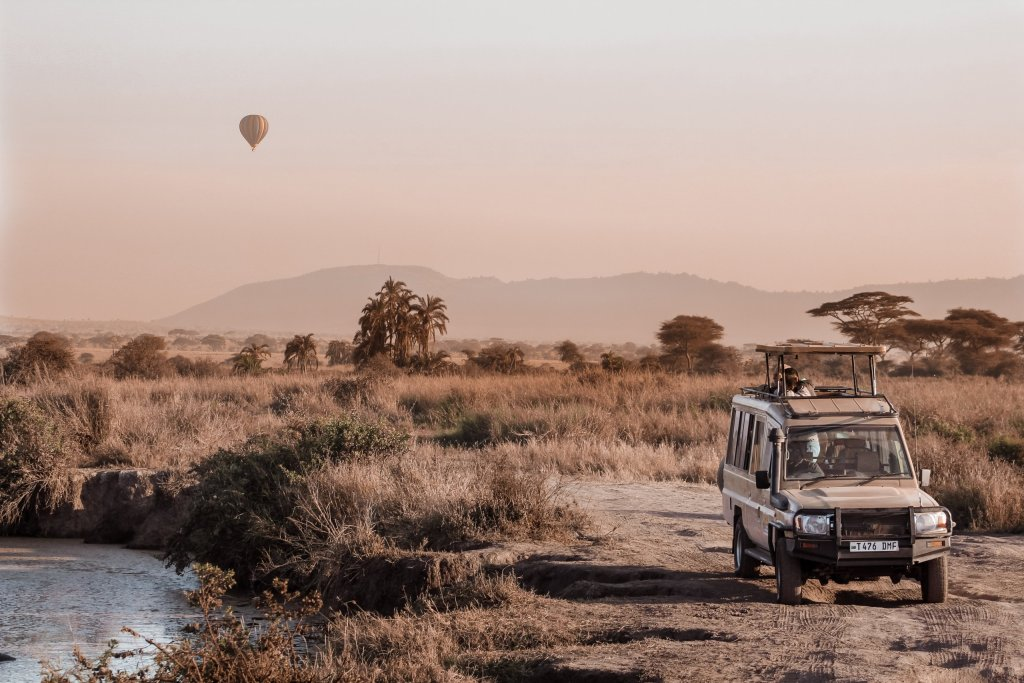 A typical sight on your Tanzania Camping Safari- a safari vehicle with a hot air balloon in the sky behind.