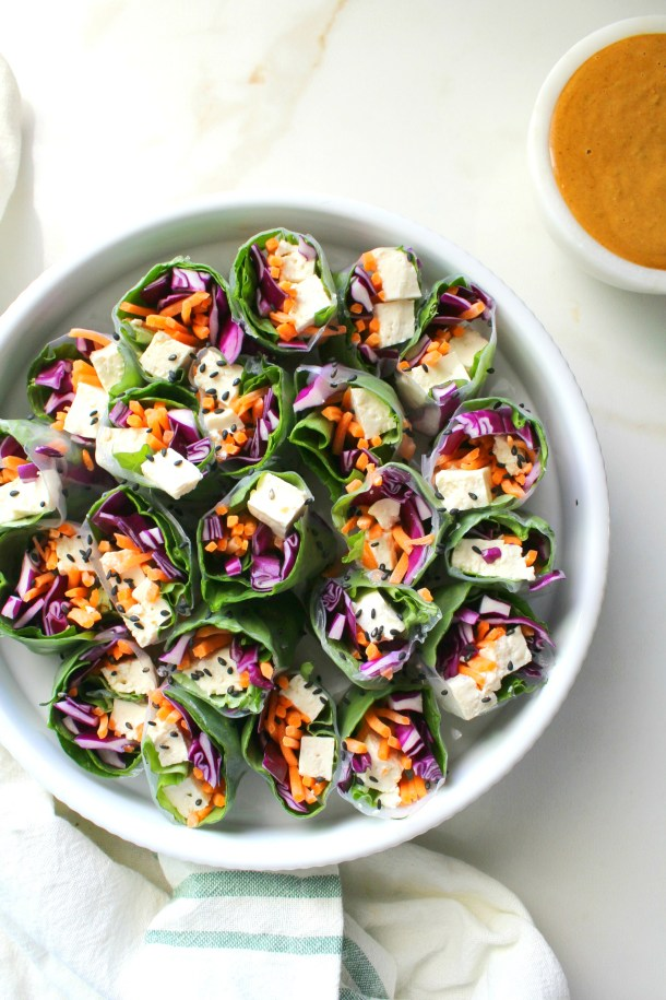 A simple lunch or dinner, these Vegan Rice Paper Rolls with Spicy Peanut Sauce are packed full of fresh veggies. Served with the best peanut sauce you've ever had!   ThisSavoryVegan.com #vegan #raw #mealprep