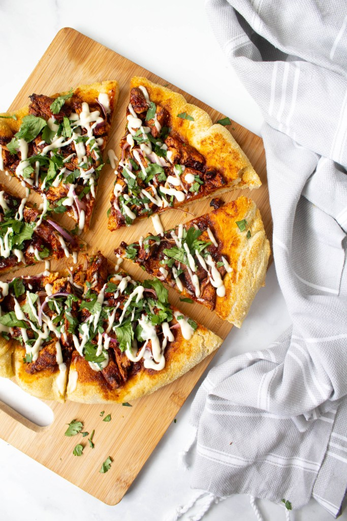 This Vegan BBQ Chicken Pizza is made extra crispy and delicious by using a cast iron skillet. Top it off with vegan ranch and fresh cilantro! | ThisSavoryVegan.com #thissavoryvegan #vegan #veganpizza