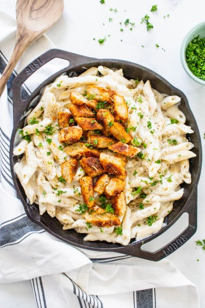 This Vegan Chicken Alfredo Pasta is the ultimate comfort meal! The sauce is lightened up by using a cauliflower base and the chicken is smoky and flavor-packed | ThisSavoryVegan.com #thissavoryvegan #veganalfredo #veganpasta