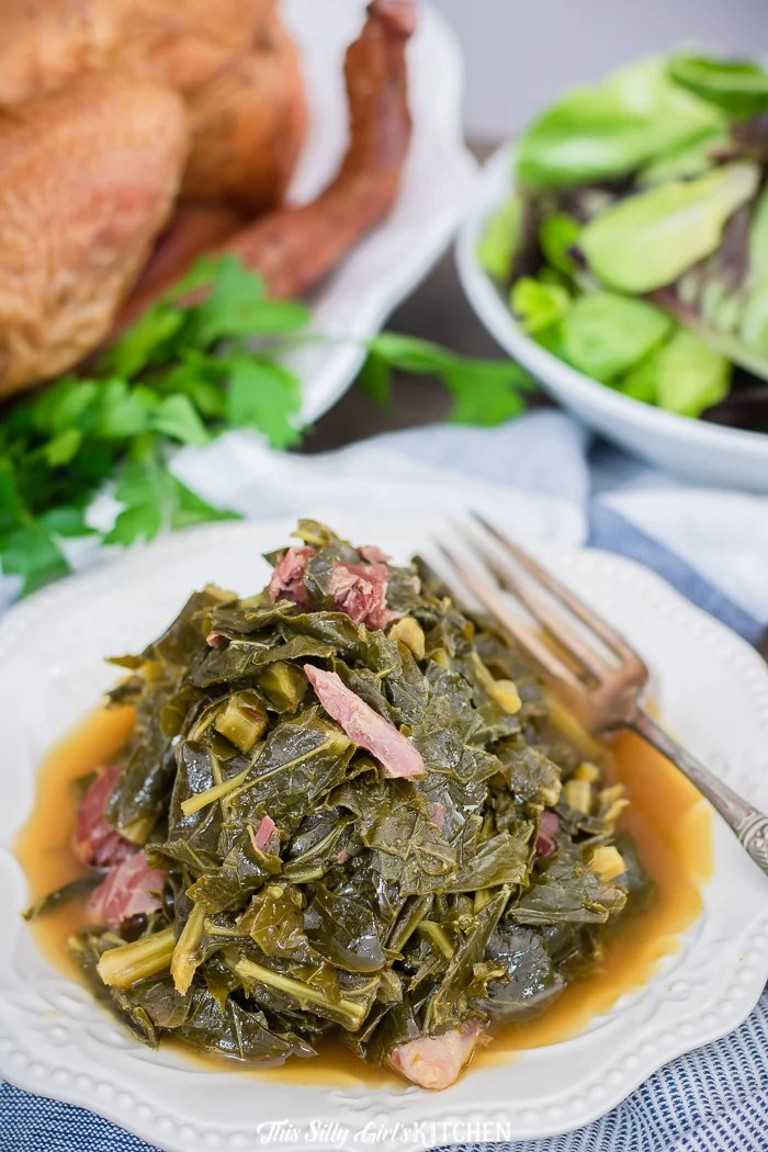 Southern Collard Greens on white plate with ham pieces sticking out.