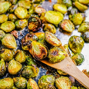 Square image of finished Brussel Sprouts on baking pan with some on wooden spoon.