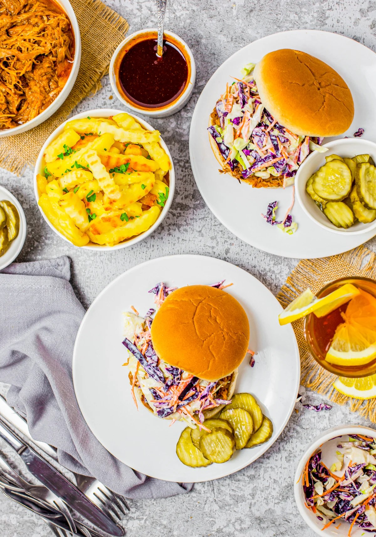 Overhead photos of two sandwiches Ono white plates with sides surrounding it
