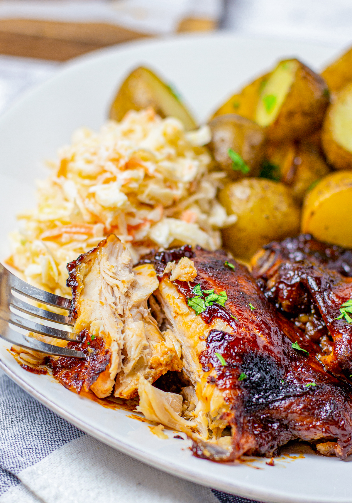 Fork pulling apart a piece of the Slow Cooker BBQ Chicken on white plate with sides