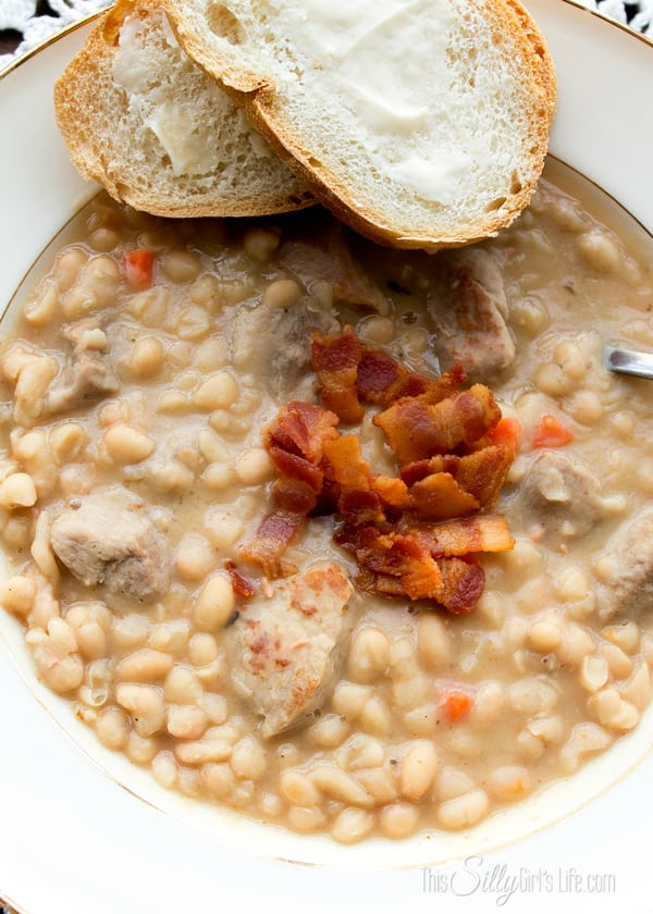Creamy White Bean and Pork Stew, perfect for a chilly day! Large chunks of tender pork cooked with navy beans bursting with layers of flavor! Serve it with warm crusty bread and lots of butter, you'll be in Heaven! Oh yea, there's BACON too! Recipe from https://ThisSIllyGirlsLife.com
