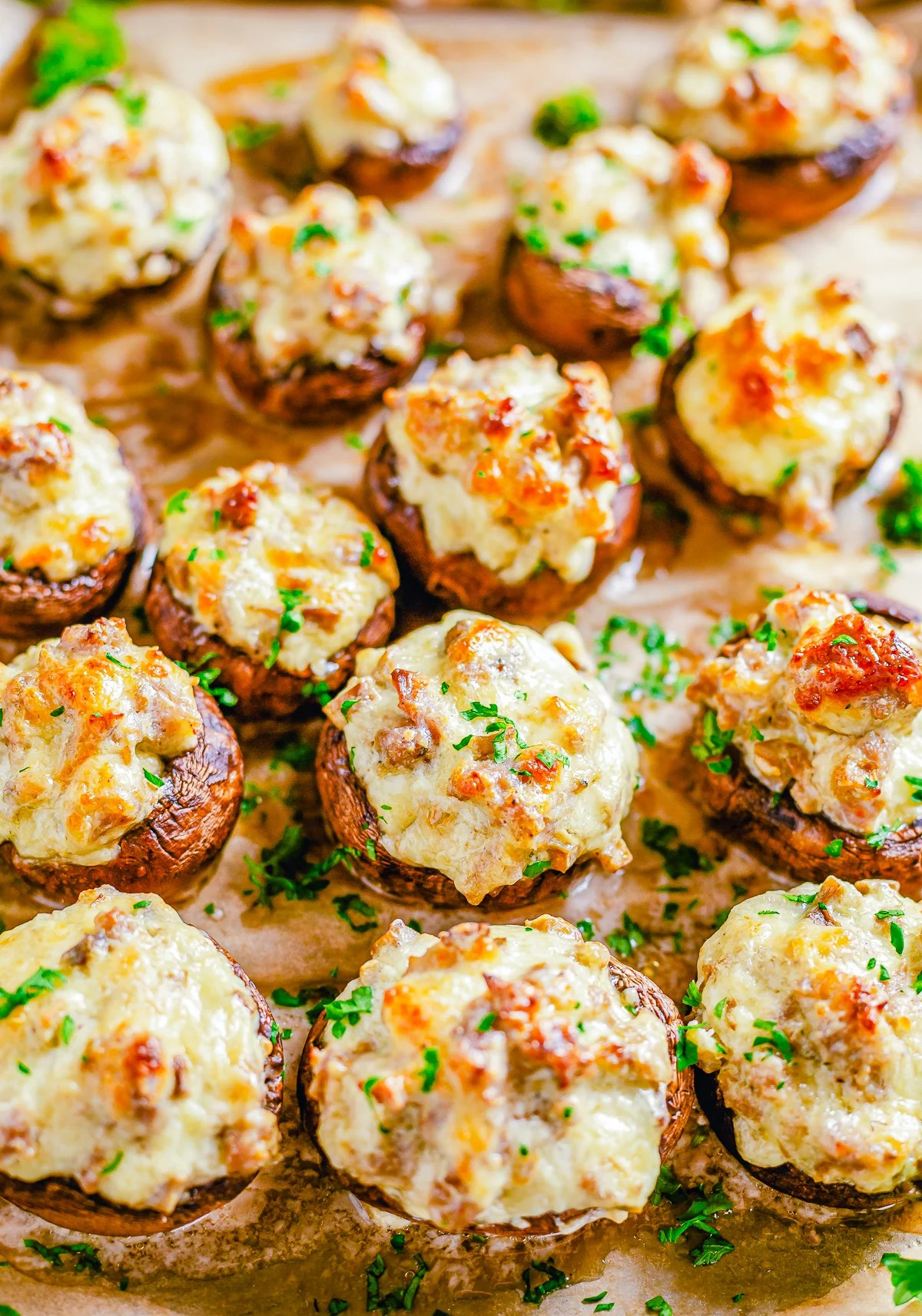 Overhead close up of finished Sausage Stuffed Mushrooms on wooden board.