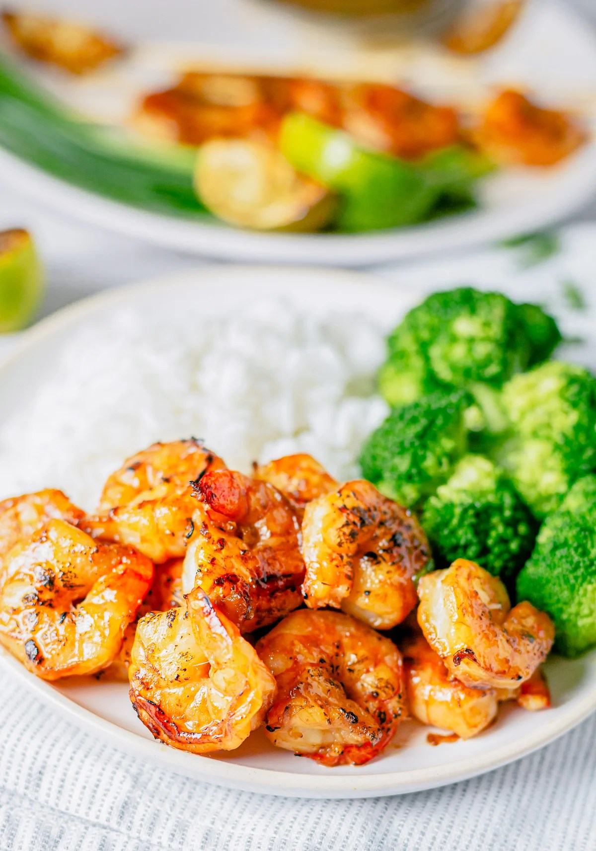 Shrimp off skewer on plate with rice and broccoli