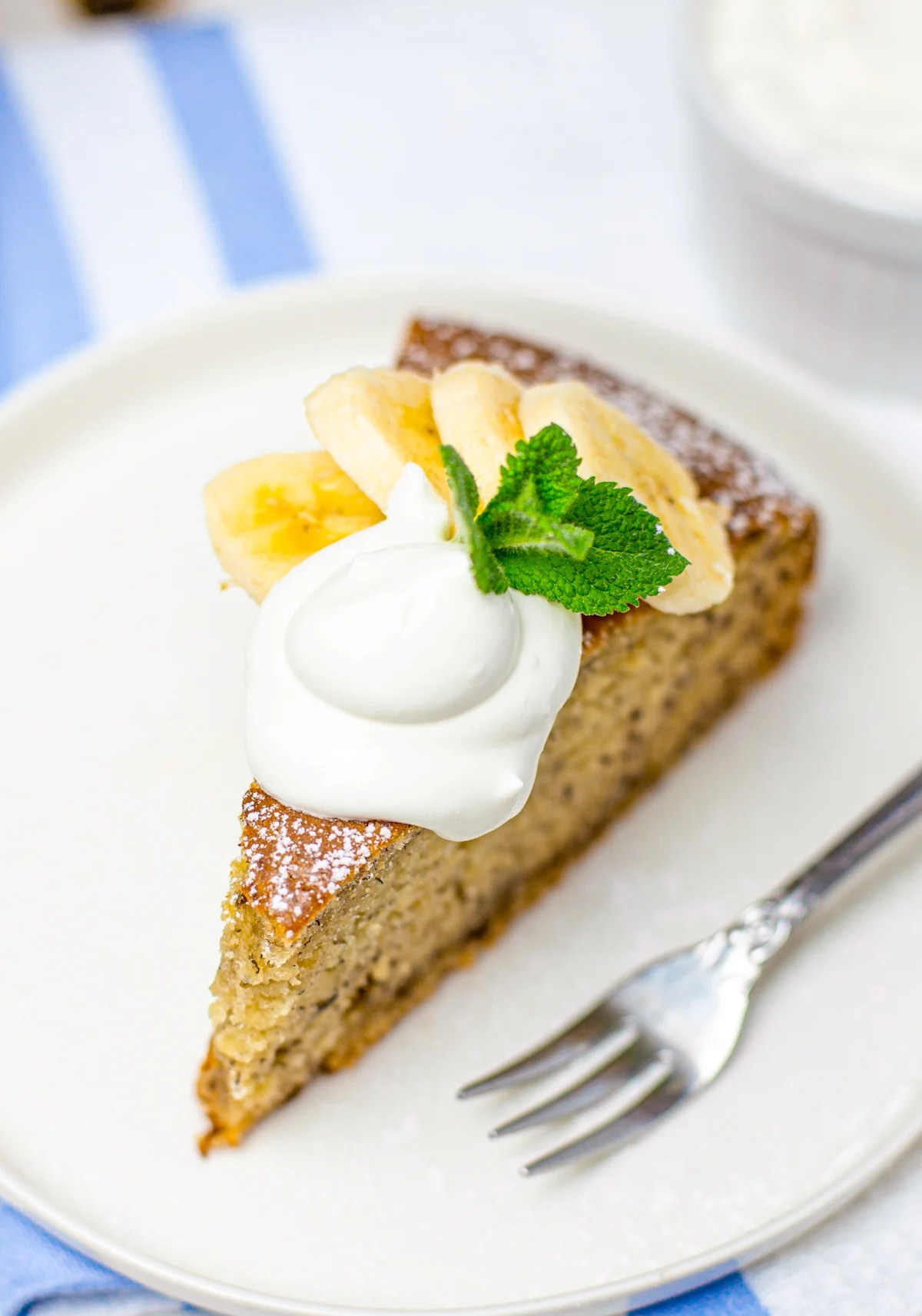 Overhead of a slice of Banana Cake on white plate garnished