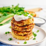 Square image of stacked cakes on white plate topped with sour cream and scallions.