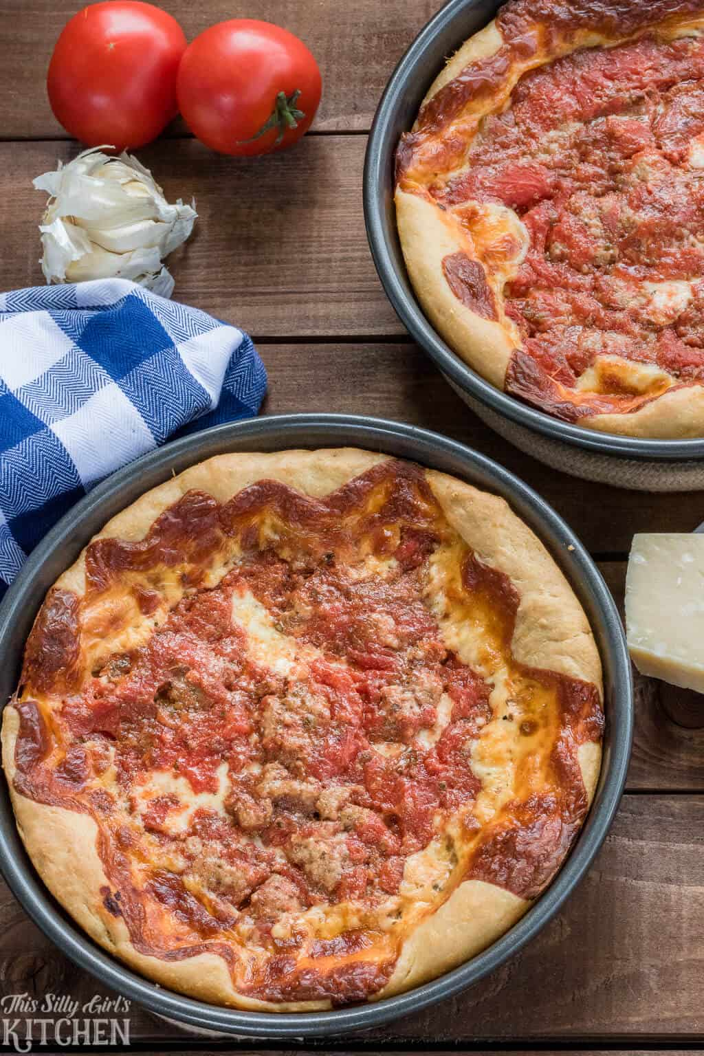 Deep dish pizzas overhead in two baking pans