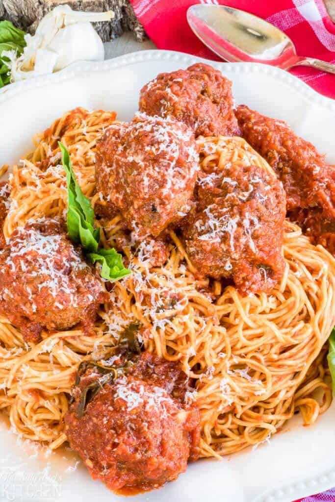 Very close up of Spaghetti and Meatballs Recipe on white plate with basil