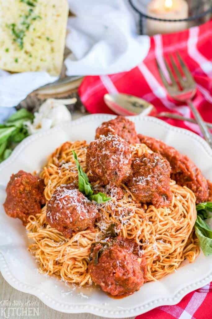Spaghetti and Meatballs piled on white plate garnished with basil