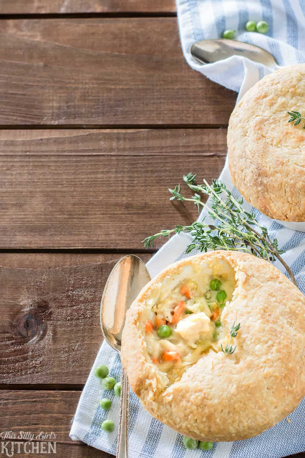 overhead of two pies with spoon and fresh herbs