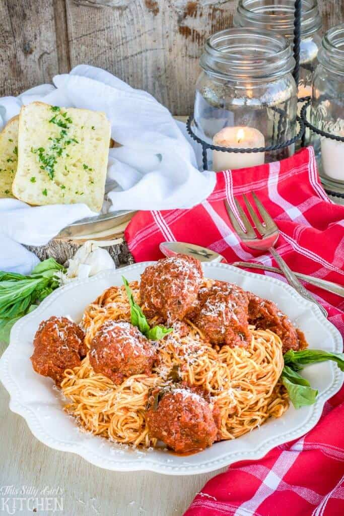 Spaghetti and Meatballs on white plate with garlic bread in background