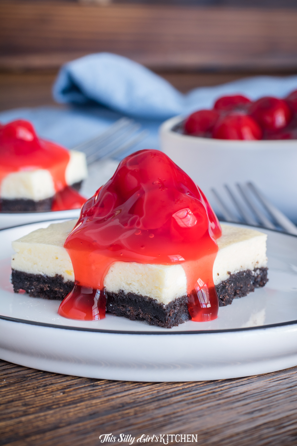 Cheesecake Bars, silky cheesecake on an addictive Oreo crust, topped with cherries! #recipe from thissillygirlskitchen.com #cheesecake #cheesecakebars #oreocheesecake #cherrycheesecake