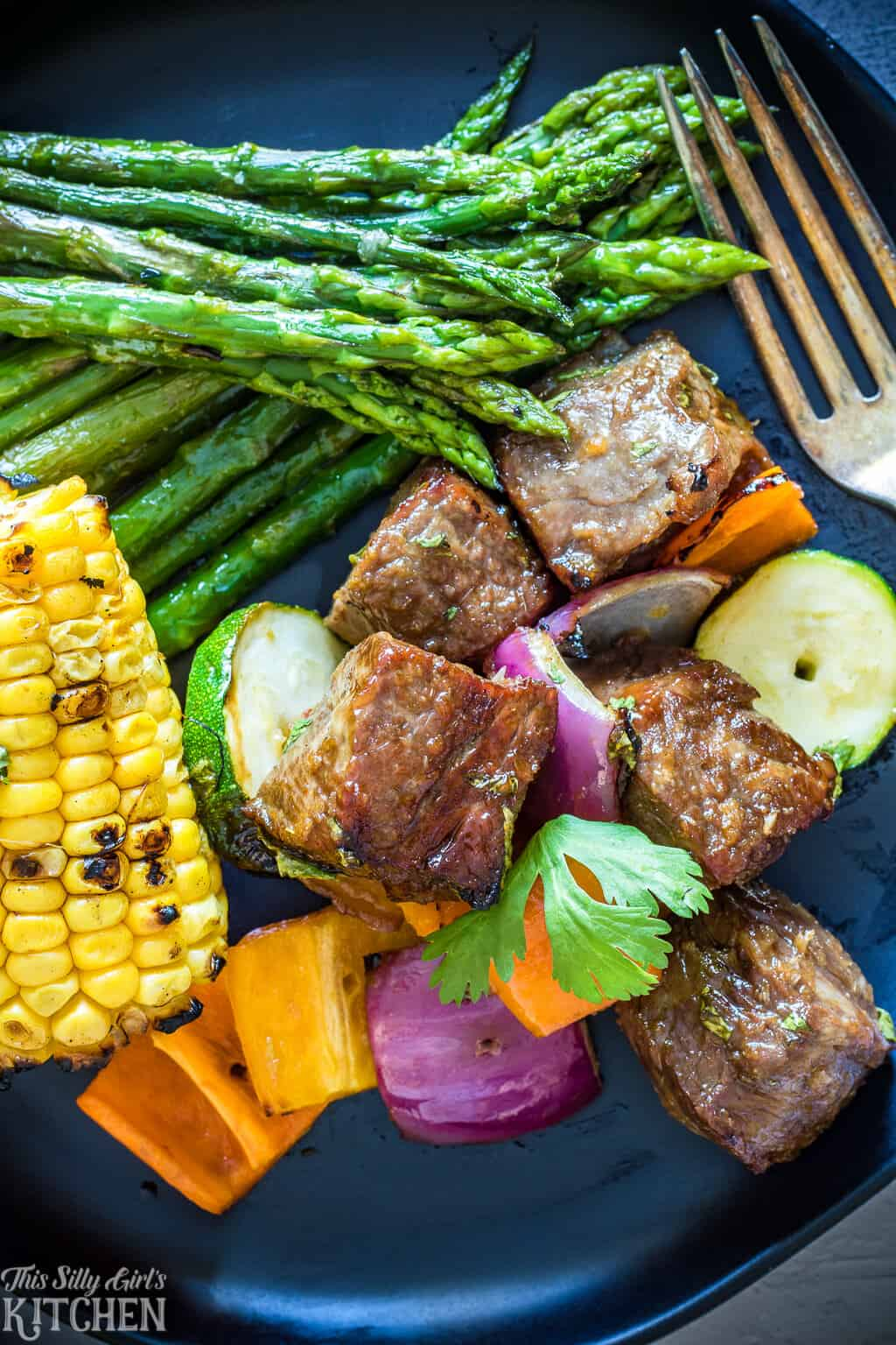 Close of Steak Kabob Recipe plated with corn and asparagus