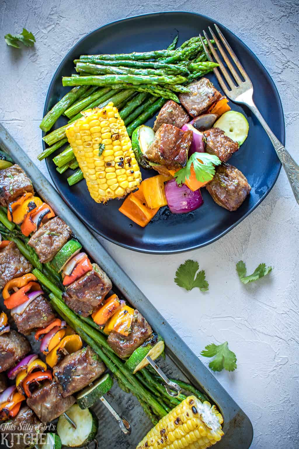 Overhead image of plated Kabobs with corn and asparagus.