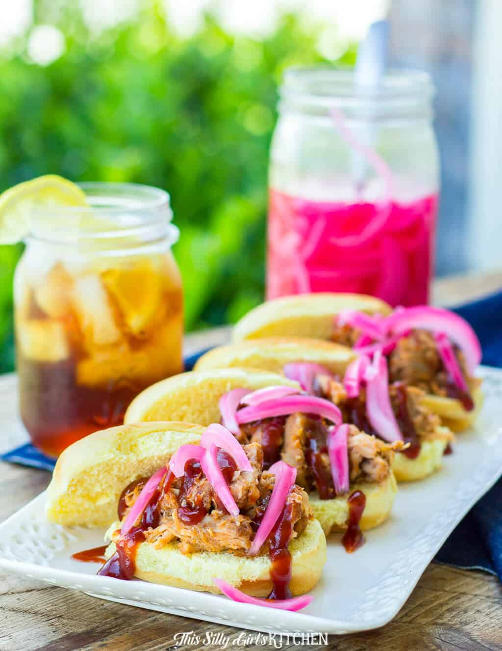 Pulled Pork Sliders on white platter in row topped with pickled onions