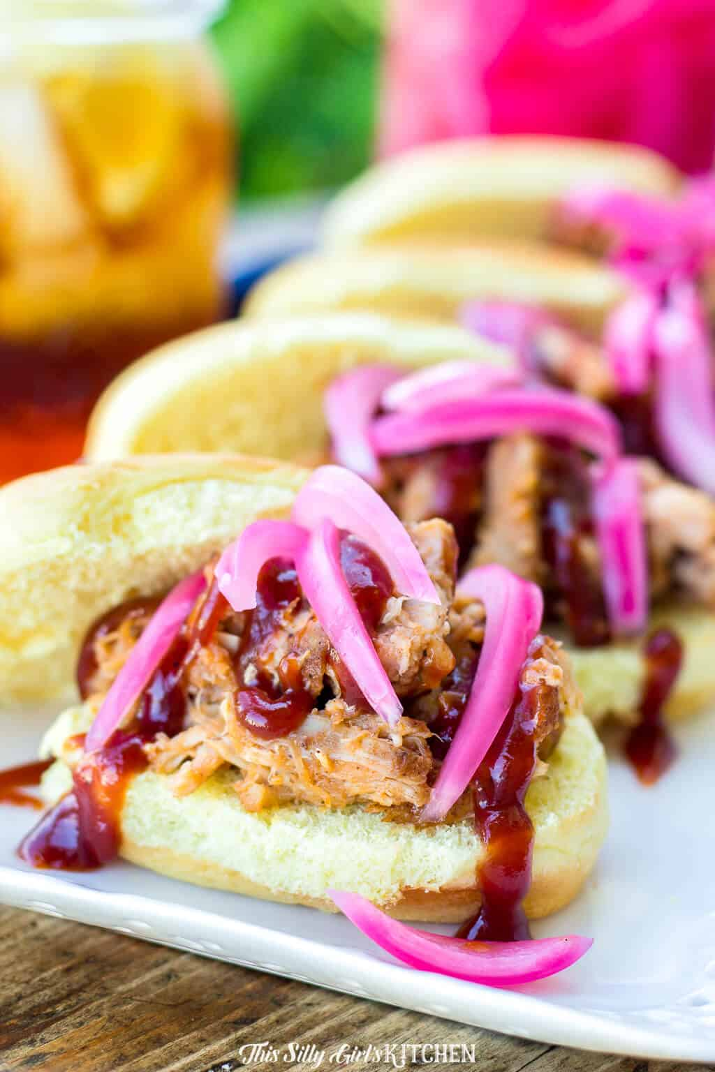 Pulled Pork Sliders topped with pickled onion on white platter