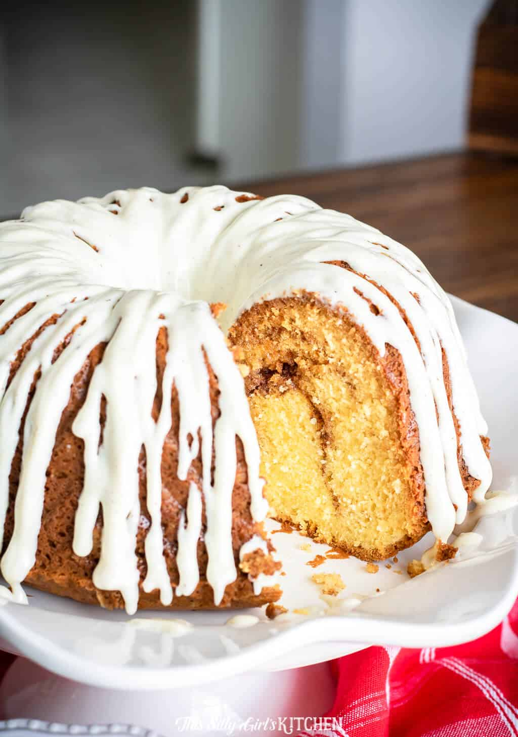 Sour Cream Coffee Cake on cake stand glazed with piece missing
