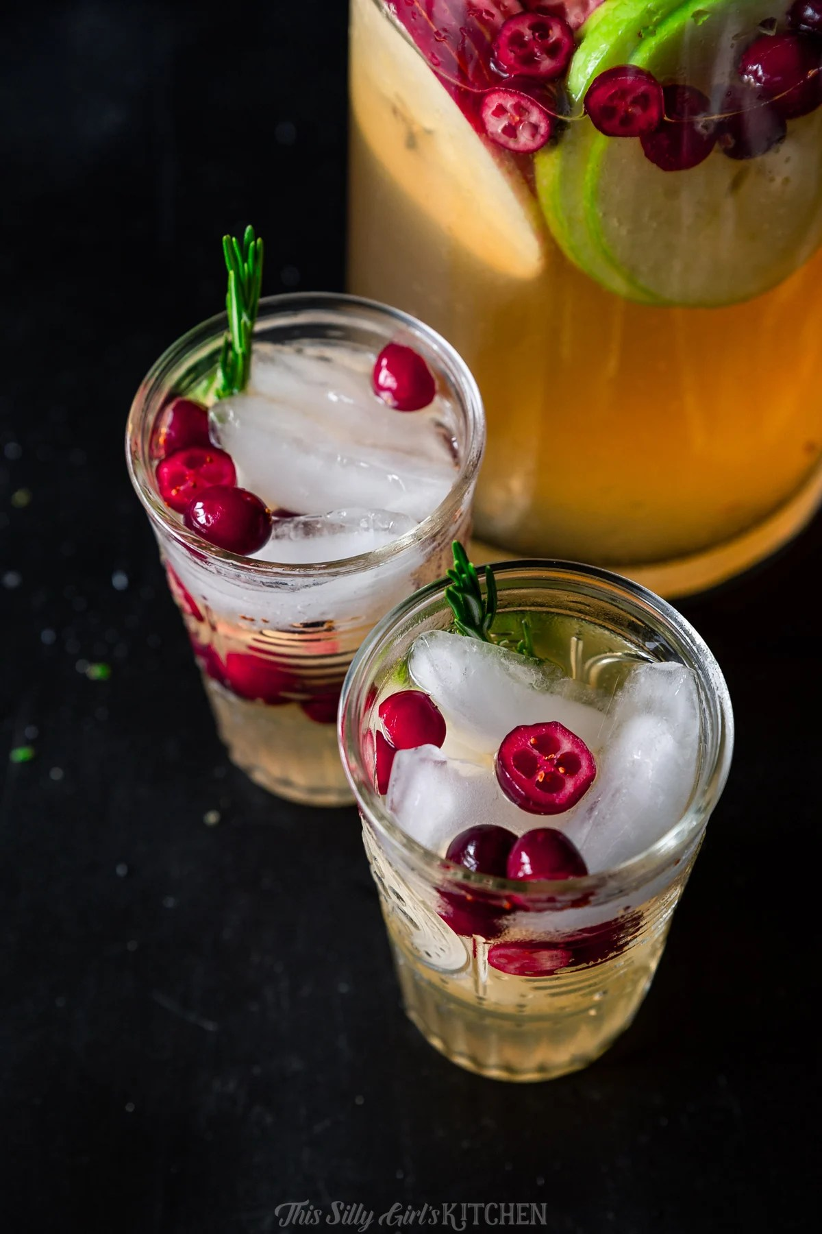 Overhead of white wine sangria in glasses with pitcher in background