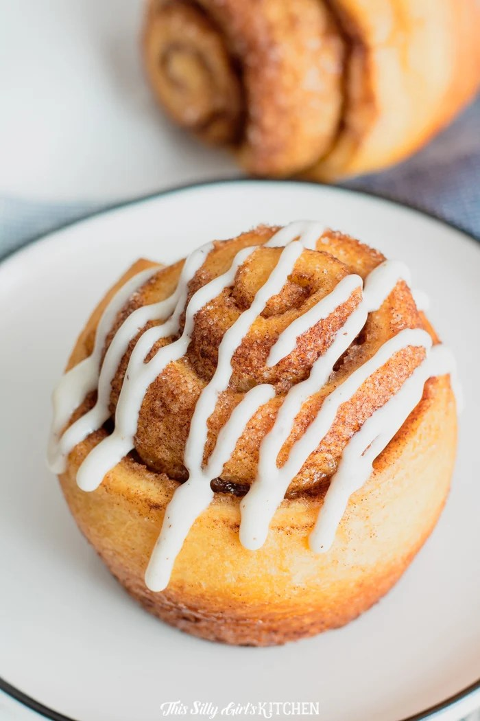 One cinnamon roll glazed on white plate
