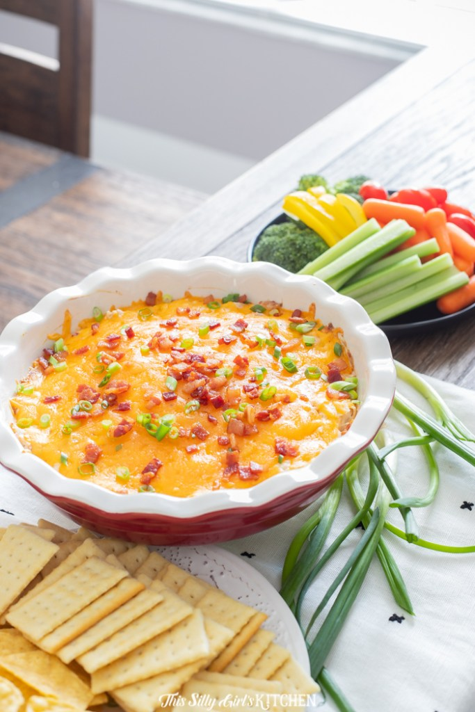 Ranch flavored cream cheese loaded with bacon, cheddar, and rotisserie chicken! #recipe from ThisSillyGirlsKitchen.com #chickendip #diprecipe #hotdip #crackchickendip #bacon #ranch #ranchdip #bacondip #hotchickendip #appetizer #superbowl #superbowlfood #tailgating