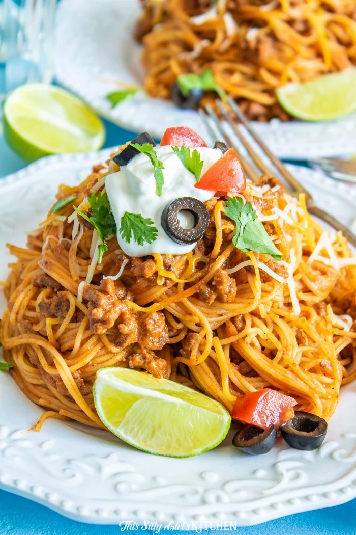 Taco Pasta on white plate topped with sour cream, olives and tomatoes