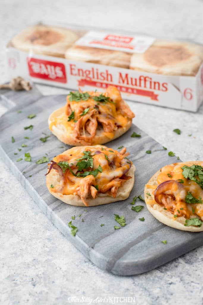 Mini BBQ Chicken Pizzas - English muffins topped with shredded bbq chicken, Colby jack cheese, red onions, and cilantro - YUM! #recipe from thissillygirlskitchen.com #pizza #minipizza #englishmuffinpizza #bbqchicken #bbqchickenpizza
