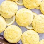 Close up overhead of lemon cookies on baking pan with lemon slices square image