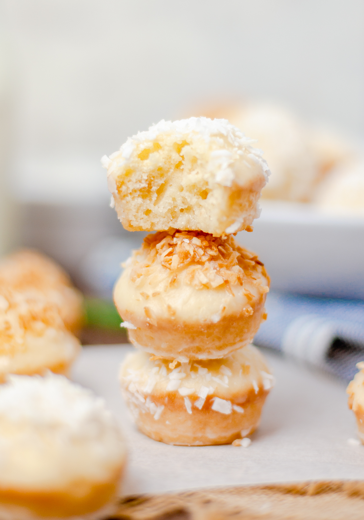 There stacked Coconut Donut Holes with bite taken out of top one