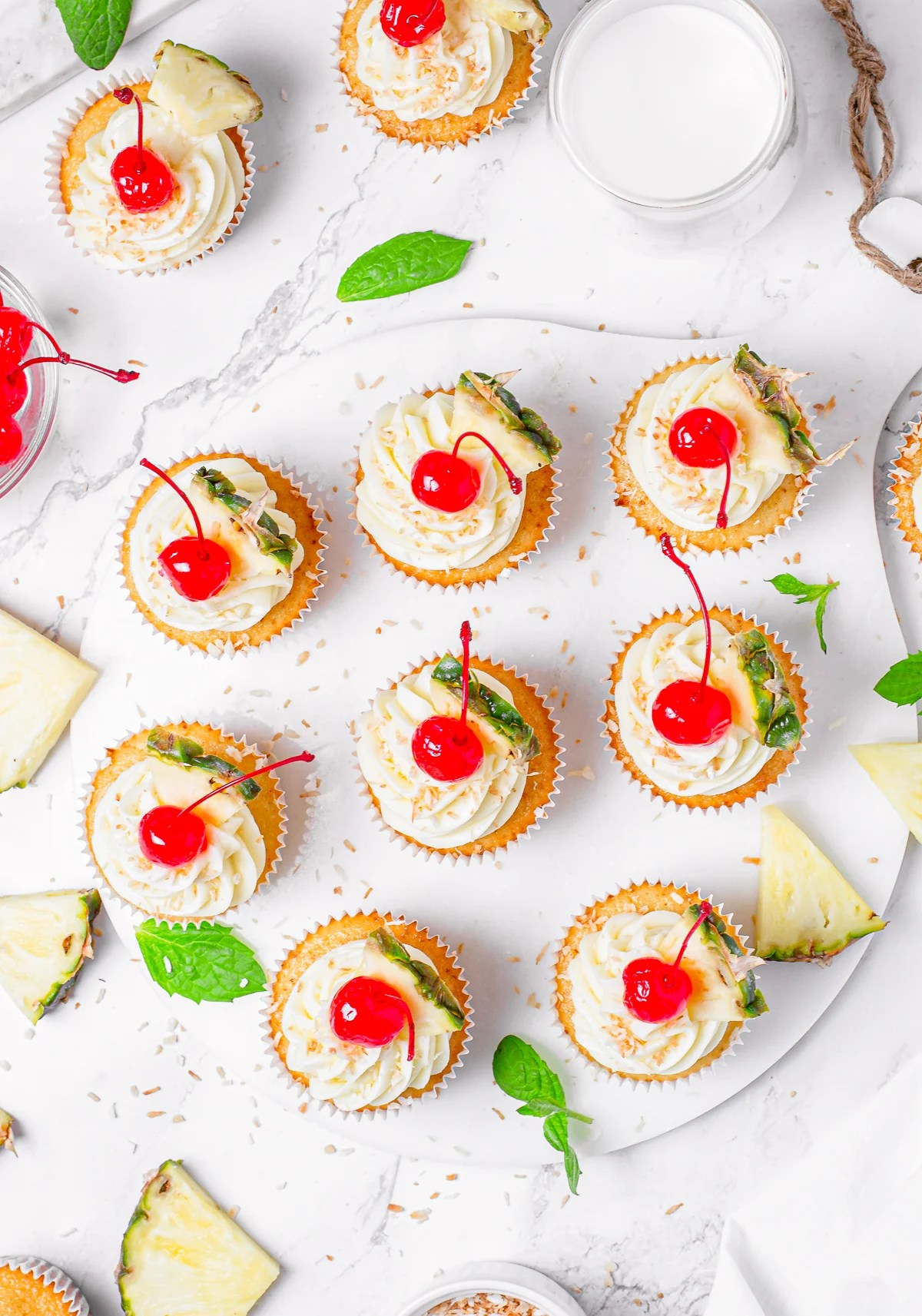 Overhead of cupcakes on white platter with pineapple surrounding it