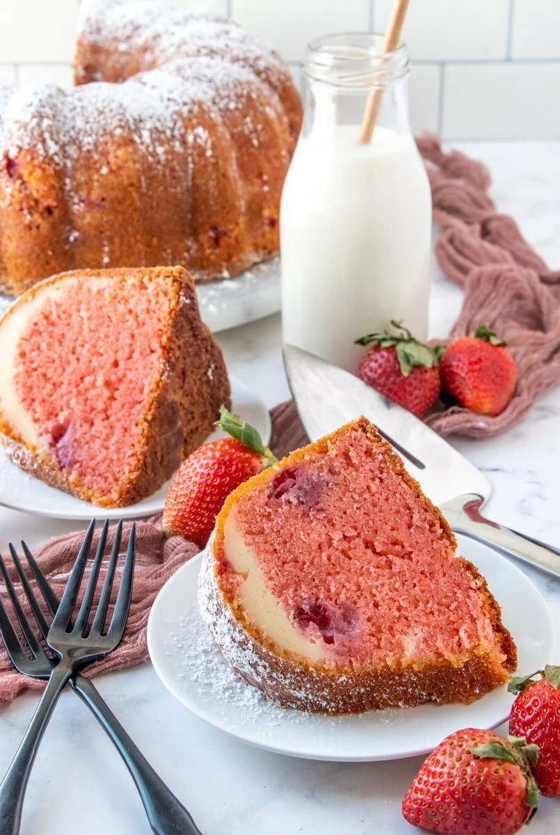 Slices of Strawberry Cheesecake Bundt Cake on two white plate with whole cake in background