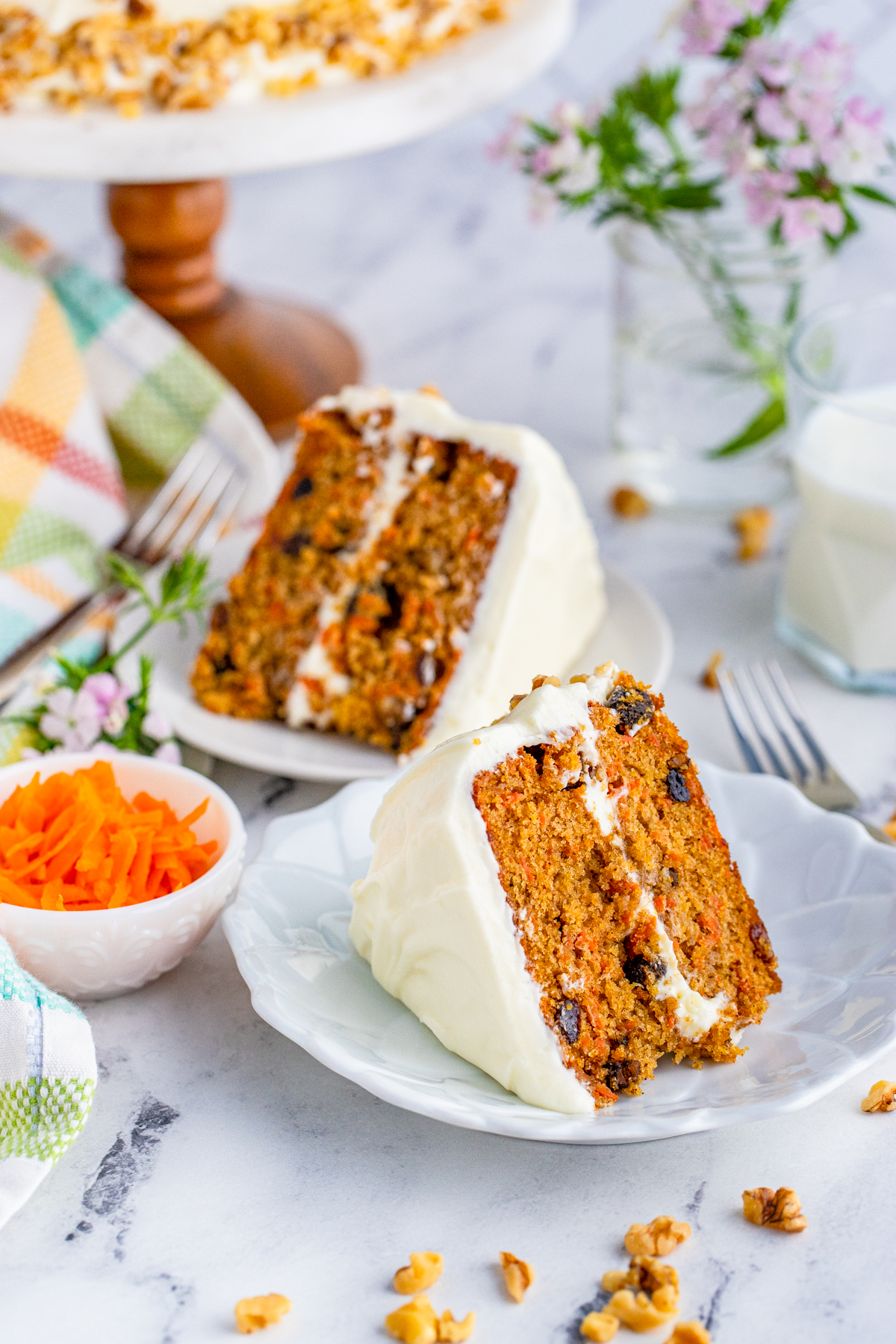 Two slices of Carrot Cake on white plates