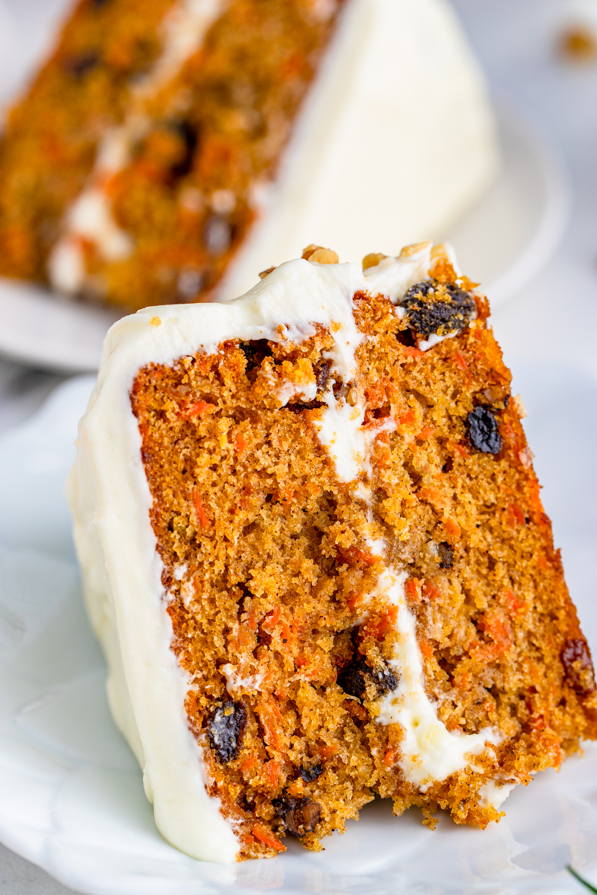 Close up of a slice of Layered Carrot Cake on white plate