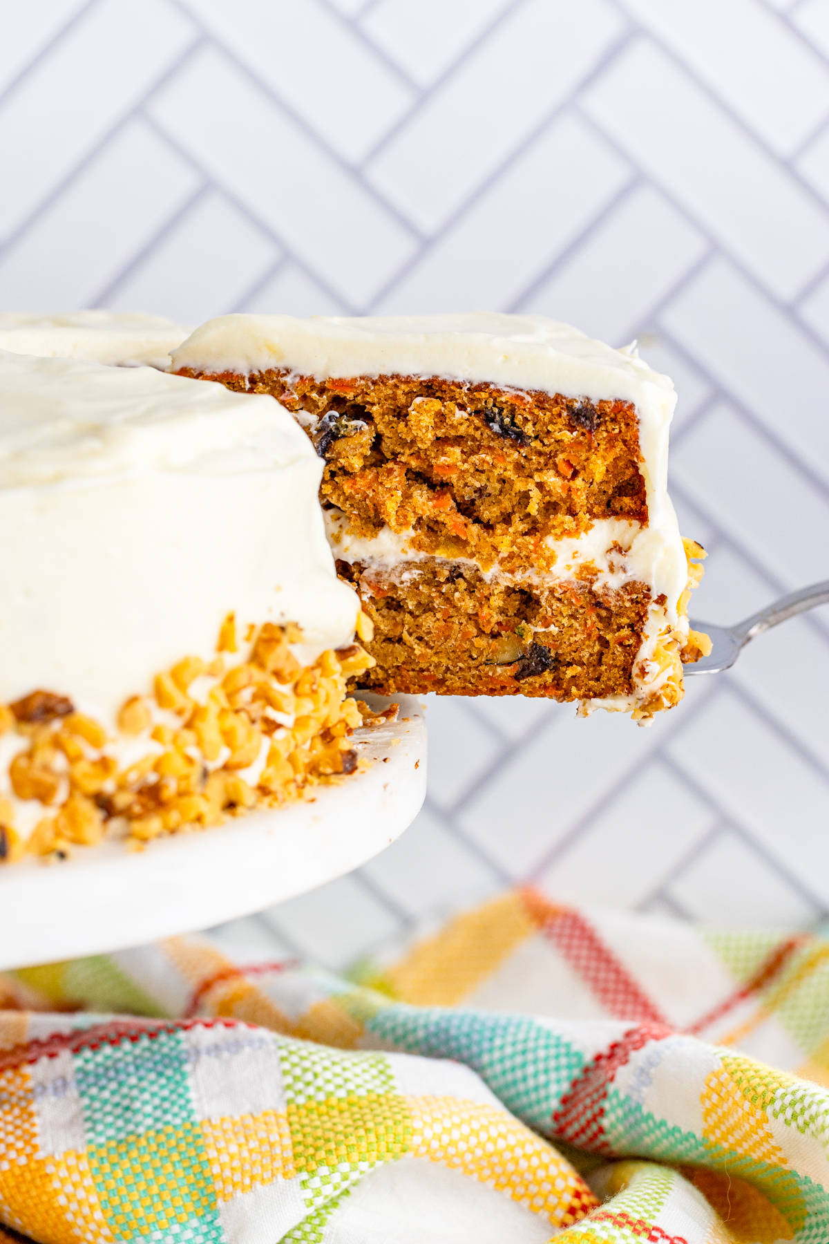 Cake server pulling out slice of Carrot Cake