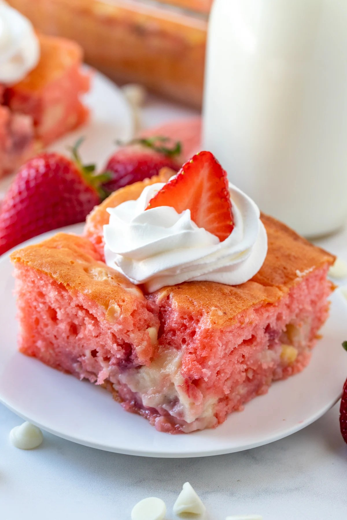 Slice of Strawberry Earthquake Cake on white plate topped with whipped cream and strawberry