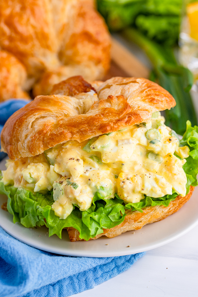 Egg Salad Sandwich Recipe in a croissant with lettuce on plate