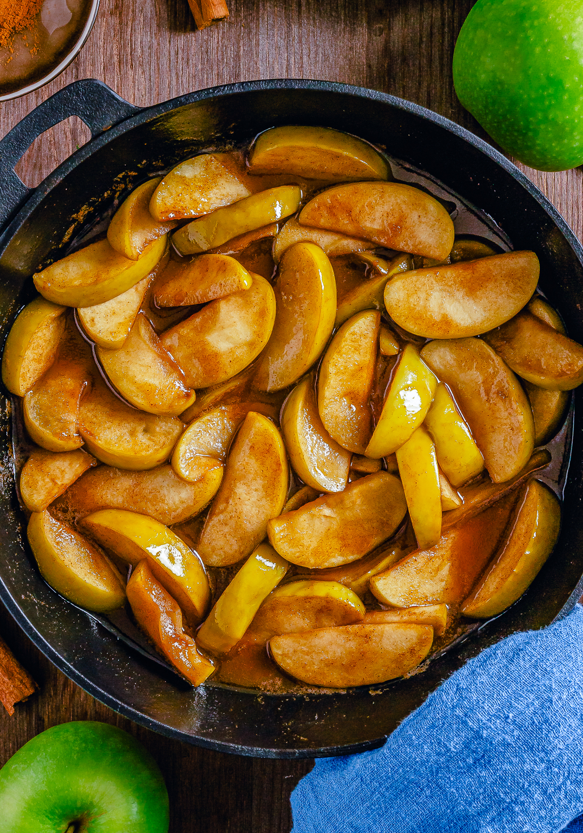 Overhead photo of Fried Apples in cast iron skillet with apples on sides.