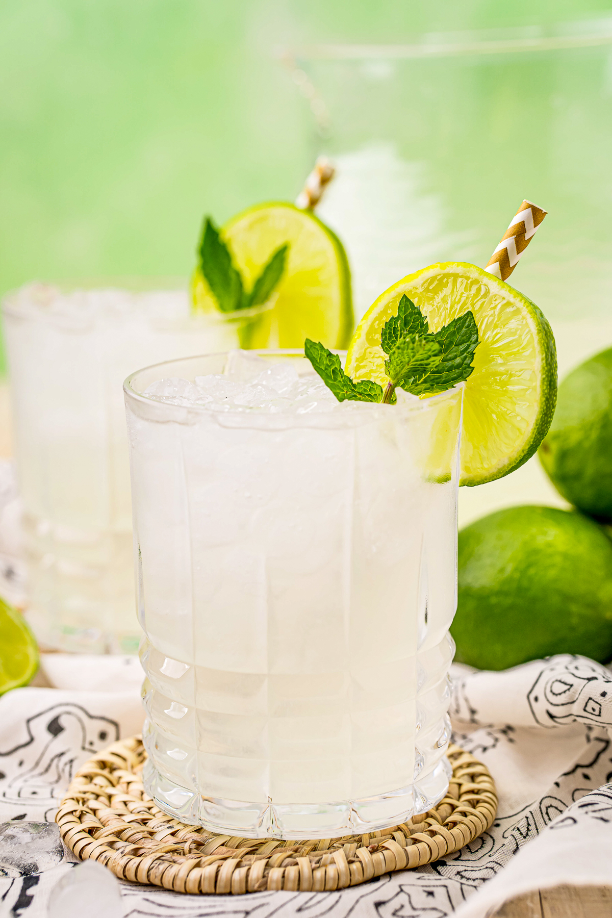 Close up of one glass of the Limeade Recipe garnished with straw, mint and limes