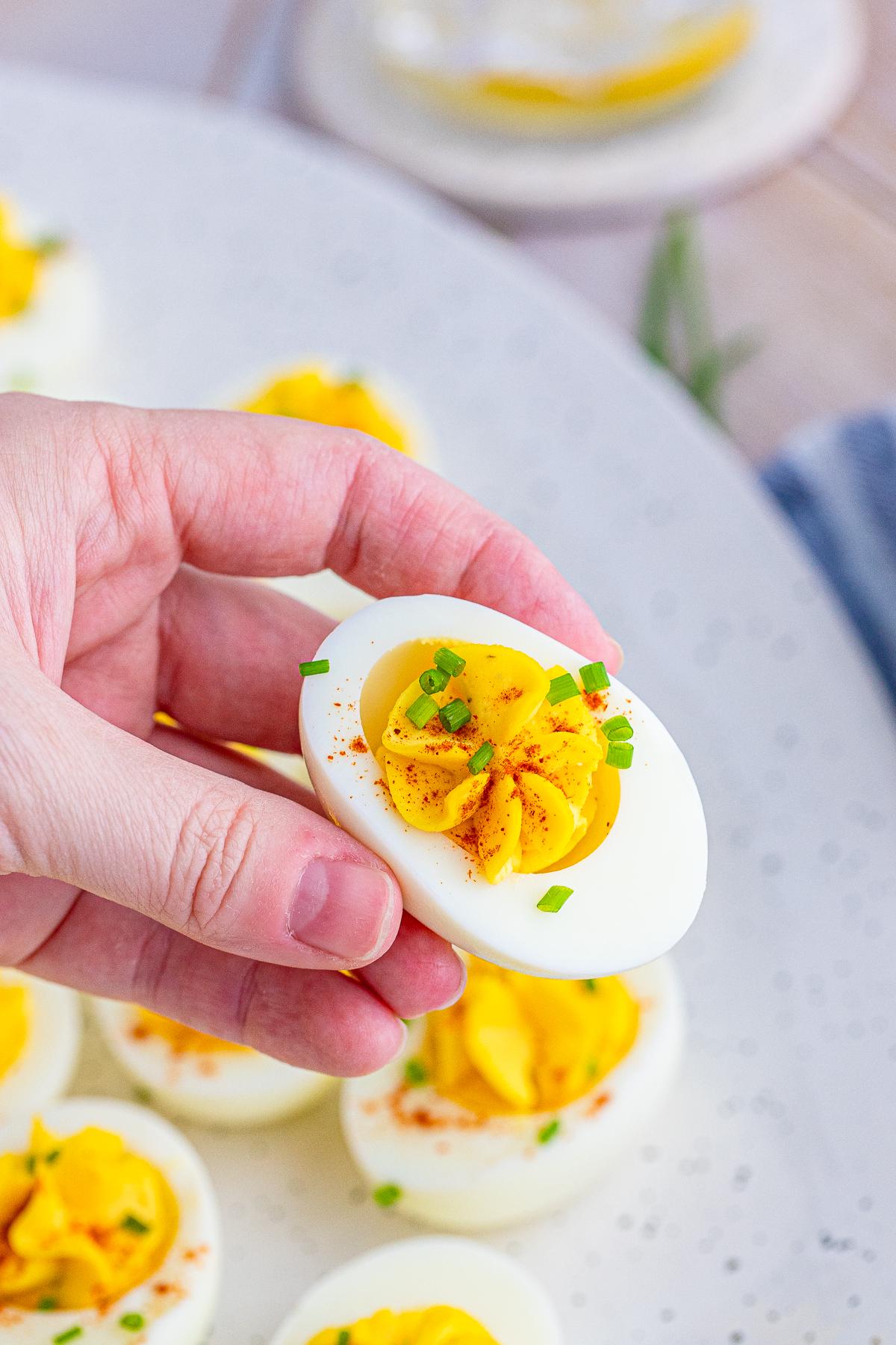 Hand holding on Easy Deviled Egg Recipe