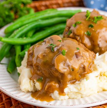 Two Salisbury Steaks on potatoes with beans square image.